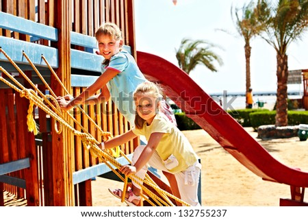Happy children move out to slide in playground.