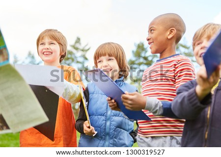Happy children on a treasure hunt as a scavenger hunt in nature with clipboard