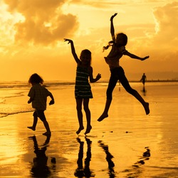 Happy children playing at the beach at the dawn time