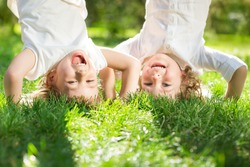 Happy children playing head over heels on green grass in spring park