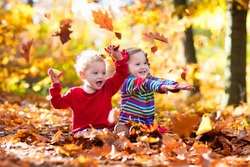 Happy children playing in beautiful autumn park on warm sunny fall day. Kids play with golden maple leaves. Focus on girl.