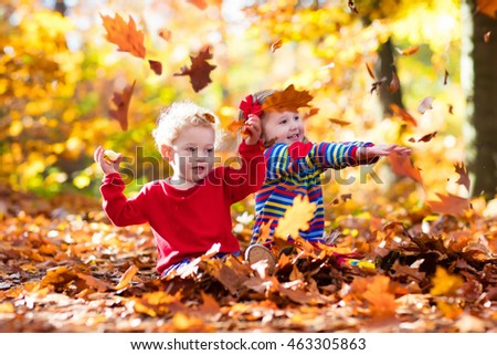 Happy children playing in beautiful autumn park on warm sunny fall day. Kids play with golden maple leaves. Focus on girl. #463305863