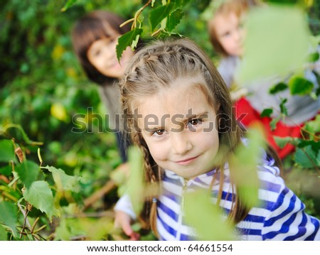 Happy children playing in nature, park, tree leaves