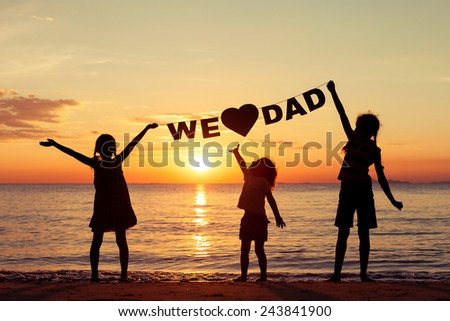 Happy children playing on the beach at the sunset time. Children hold in the hands  inscription \