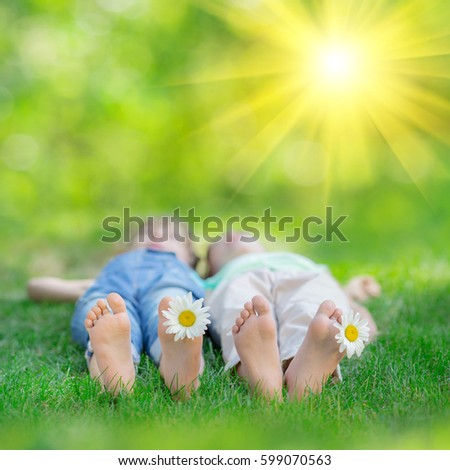 Happy children playing outdoors. Kids having fun in spring park. Couple lying on green grass #599070563