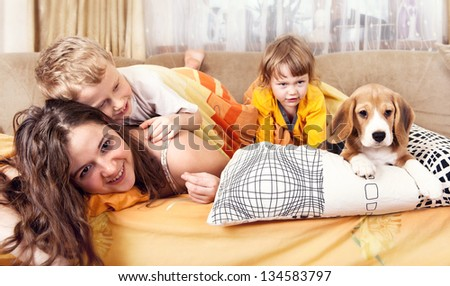 Happy children playing with beagle puppy in bed