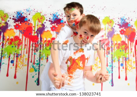 Happy children playing with paints