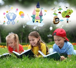 Happy children reading books on green grass outdoors