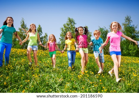 Happy children run and hold hands in green field #201186590