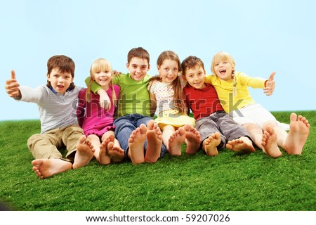 Happy children sitting on green grass