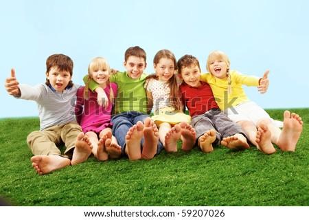 Happy children sitting on green grass - stock photo