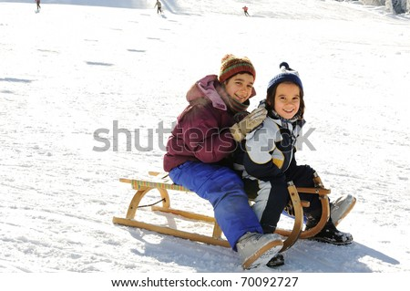 Happy children sledding on snow, mountain park