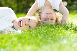 Happy children standing upside down on green grass. Boy and girl in spring park. Healthy lifestyles concept.