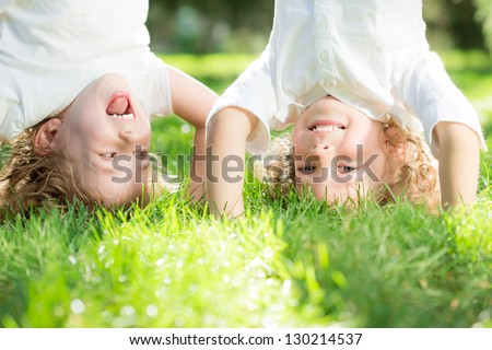 Happy children standing upside down on green grass in spring park. Healthy lifestyles concept. #130214537