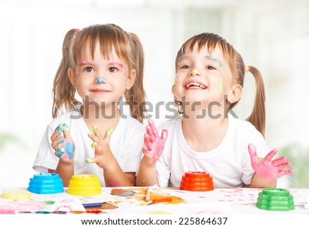 happy children twins girl draws paints , get dirty