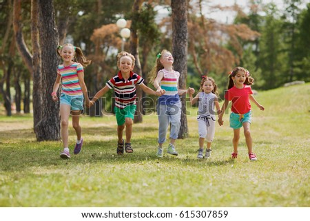 Happy children walking together in park and holding hands on a wonderful summer day #615307859