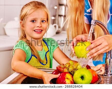 Happy children washing fruit at kitchen.