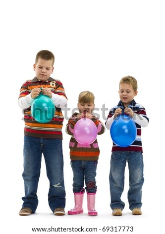 Happy children wearing jeans and striped t-shirt, holding colorful toy balloons, laughing. Isolated on white background.?