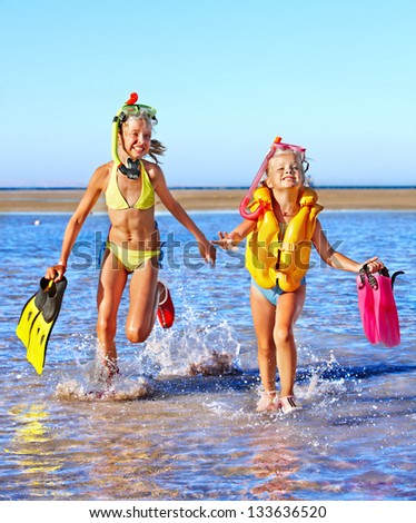 Happy children with flippers running on  beach.