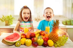 Happy children with fruits and fresh juice in kitchen, kids healthy eating concept