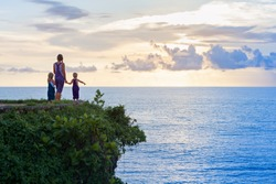 Happy children with mother have fun on summer beach holiday. Funny little kids stand at sea cliff. Looking at beautiful view of sunset sky. Healthy family lifestyle, summer travel on tropical island.