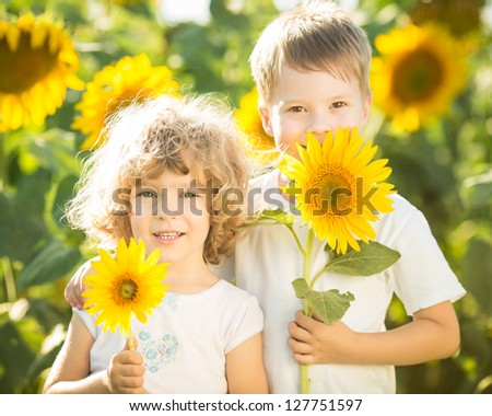 Happy children with sunflower playing in spring field