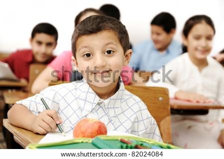 Happy children with their teacher in classroom, doing schoolwork - stock photo
