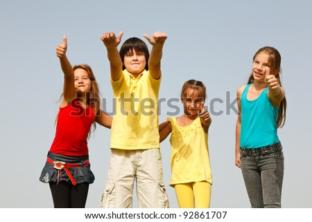 Happy children with thumbs up, in the nature