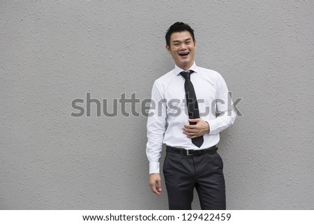 Happy Chinese business executive laughing and standing in front of a grey wall. Chinese businessman laughing. Image has been composed with copyspace to the left