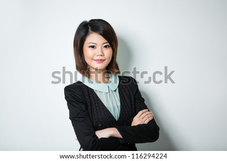 Happy Chinese business woman leaning against a wall.