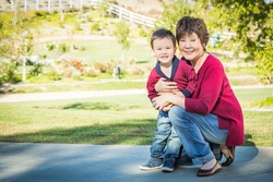 Happy Chinese Grandmother Having Fun with Her Mixed Race Grandson Outside.