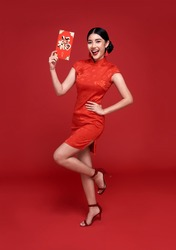 Happy Chinese new year. Asian woman wearing traditional cheongsam qipao dress holding angpao or red packet monetary gift isolated on red background.