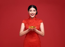 Happy Chinese new year. Asian woman wearing traditional cheongsam qipao dress holding gold ingot that Represents wealth and prosperity isolated on red background.