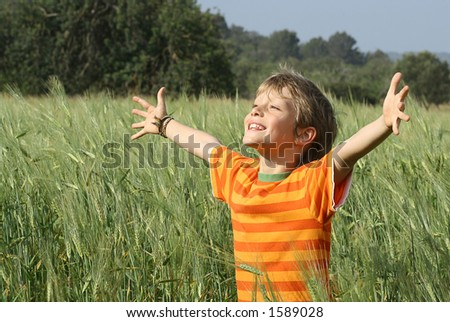 happy christian child arms raised in happiness and faith