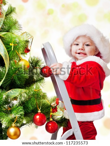 Happy Christmas baby standing on a step ladder decorating Xmas tree