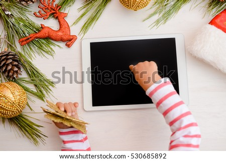 Happy Christmas background. Top view on child hands using tablet computer with toys and Santa Claus hat on light wooden table. Modern festive decoration ready for joyful message or shopping time