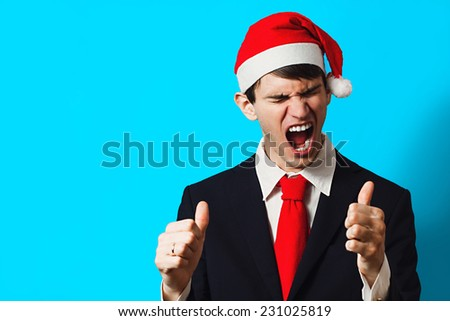 Happy christmas businessman in santa hat with thumb up on a blue background #231025819