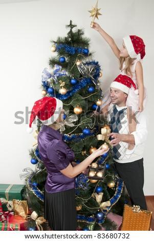 Happy Christmas - Family decorating a Christmas tree