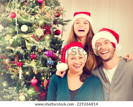 Happy Christmas Family portrait Smiling Parents with teenage daughter at Home Celebrating New Year Christmas Tree