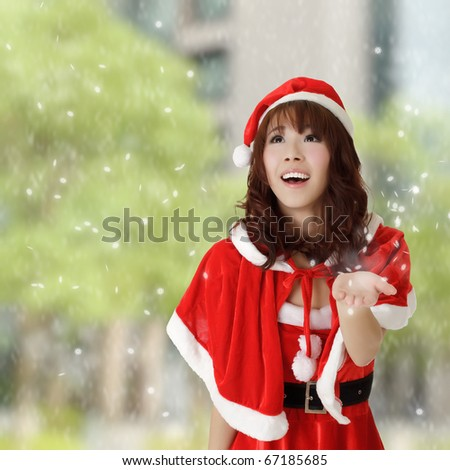 Happy Christmas girl in outside with snowflakes falling.