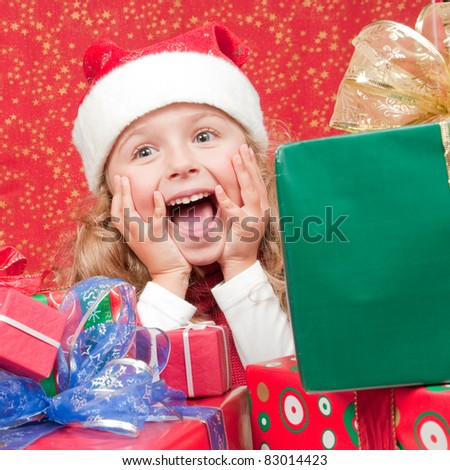 Happy Christmas - Little girl in Santa Claus hat with Christmas presents - stock photo
