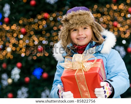 Happy Christmas - Little girl with Christmas gift  (Defocused Christmas Tree Lights)