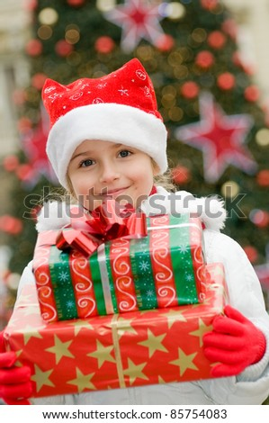 Happy Christmas - Little girl with Christmas gifts portrait - Defocused Christmas Tree Lights
