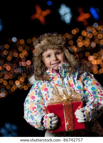 Happy Christmas night  - Little girl with Christmas gift - Defocused Christmas Tree Lights