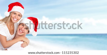 Happy christmas santa couple on the beach. Holidays.