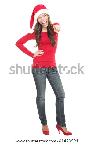Happy Christmas woman excited pointing standing in full length isolated on white background wearing red Santa hat. Beautiful Caucasian / Asian model. - stock photo