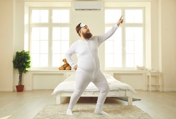 Happy chubby guy wakes up one weekend morning, gets up from bed, dances and enjoys fun free time. Funny cheerful confident fat young man in white pajamas dancing alone in light sunny bedroom at home