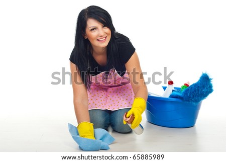 Happy cleaning woman kneel and floor wipe with a dustt cloth  and spray in her house