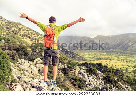 Happy climber hiker winning reaching life goal, success man at summit, successful business concept. Young runner hiker arms up outstretched,freedom and happiness rock climbing achievement in mountains