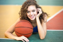 Happy closeup portrait of beautiful young female smiling with a basketball at the street ball court.